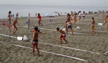 niñas y niños juegan al bádminton en la playa