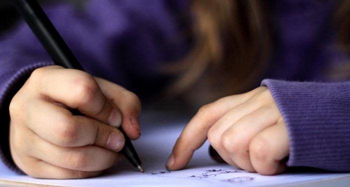 manos de niña escribiendo