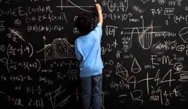 Niña y pizarra con fórmulas matemáticas
